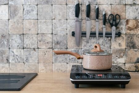 Kitchenware pan at small electric stove with control panel standing in modern kitchen on wooden surface table. Wall with marble tile and set of knives on blurred background
