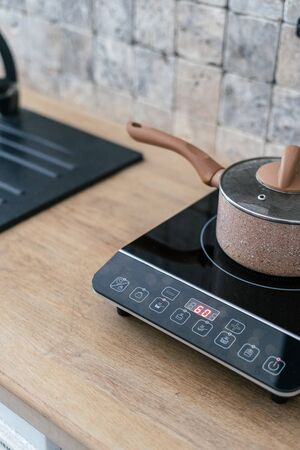 Vertical photo of kitchenware pan at small electric stove with control panel standing in modern kitchen. Marble wall tile and wooden surface table on blurred background