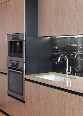 Vertical photo of modern apartment with contemporary interior. New kitchen with wooden facade at cupboard, household appliance, coffee machine and sink with chrome water tap at stone worktop