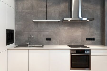Modern interior design at white contemporary kitchen in loft style. Glossy cabinet with built in household appliance, electric stove, oven, sink on worktop and extractor hood on grey wall Stock fotó