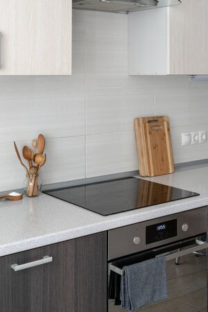 Vertical photo fo ceramic induction stove in contemporary home with wooden cutting board and spoon. Modern interior, built in oven, range hood, supplies, kitchen appliance and white tile on wall