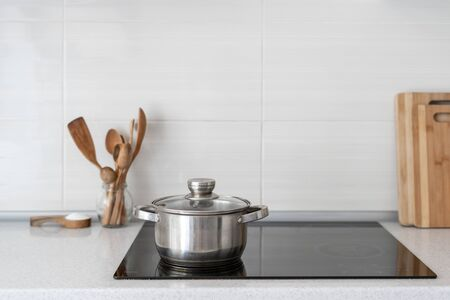 Modern apartment with contemporary interior, built in kitchen appliance, white tile on wall and copy space. Black ceramic induction stove with saucepan on clean surface and wooden supplies Stock fotó