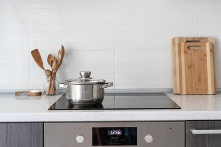 Black ceramic induction stove with timer on control panel and saucepan on top. Contemporary home with modern interior, built in kitchen appliance and white tile on wall with copy space Stock fotó