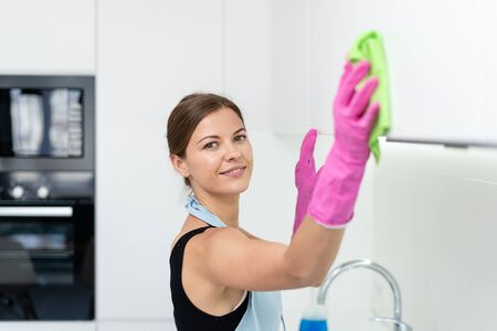 Selective focus of smiling young adult woman in apron and rubber gloves using wipe cloth and cleaning kitchen cabinet at home, looking at camera