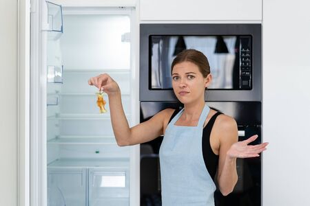 Unhappy and frustrated young adult woman in apron standing on kitchen near opened empty built in refrigerator with leftover apple in hand, looking at camera Stock fotó