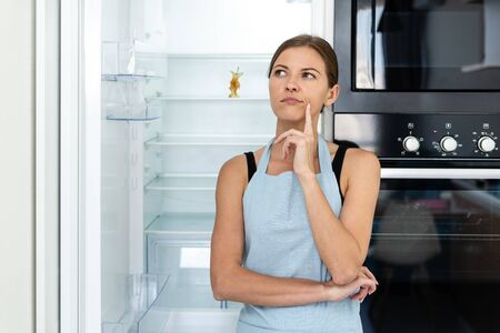 Frustrated young adult woman in apron looking away, standing on kitchen near opened built in refrigerator with apple at empty shelf