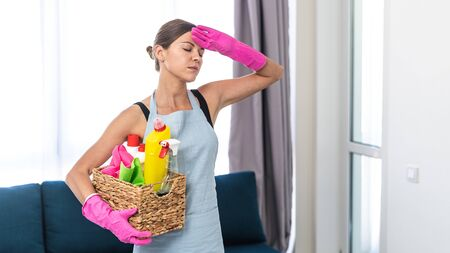 Panoramic view of tired, exhausted young adult woman in apron with wicker box of detergent and cleaning stuff, holding hand in rubber gloves on forehead