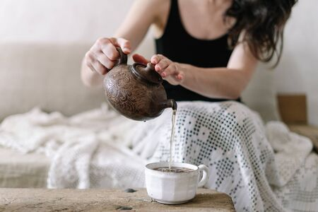 Selective focus of young adult woman holding ceramic teapot, pouring tea in white cup and resting on weekend holiday at cozy home. Girl sitting on sofa with plaid and enjoying day