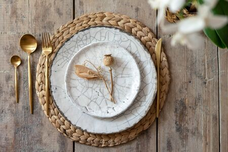 Flat lay and top view of table setting on wooden background. White plates, tableware, cutlery spoon with fork, knife lying on woven rug with decorative elements and fresh orchid flower