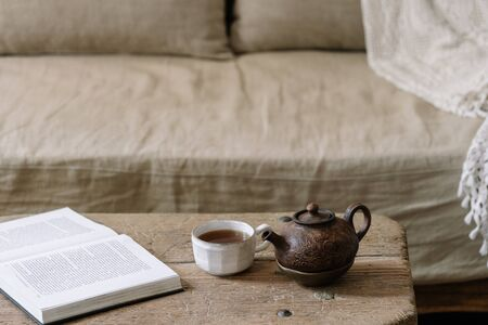 Teapot, cup with beverage, paper book and orchid flower on wood textured table near comfort couch and white wall. Cozy house with wooden interior design
