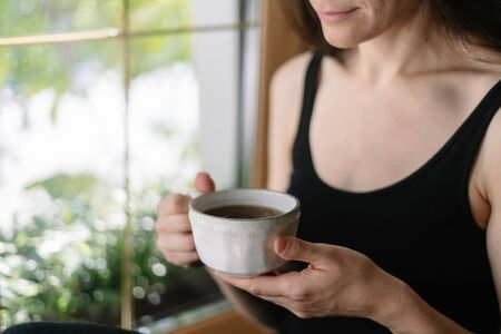 Cropped view of happy young adult woman holding white cup of beverage in hands. Smiling girl drink tea or coffee sitting on windowsill . Photo with copy space and green plants behind window