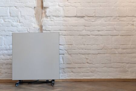 Heater near white brick wall with copy space. Contemporary electric radiator in cozy house with modern interior room Stock fotó