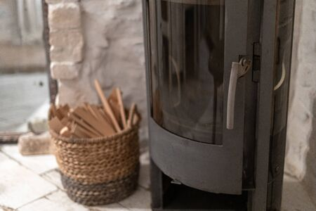 Selective focus of wood stove fireplace with metal body and glass door in comfort house with cozy interior in room. Wicker basket with firewood near chimney Stock fotó
