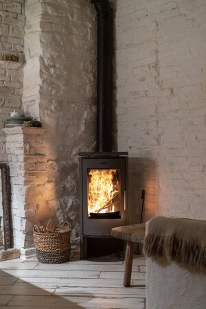 Vertical photo of wood stove fireplace with metal body and glass door in comfort house with cozy interior in room. Wicker basket with firewood near chimney with fire Stockfoto