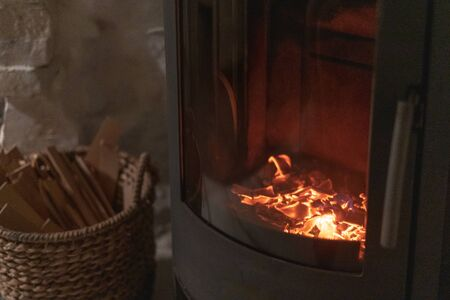 Selective focus on burning coals in wood stove fireplace with metal body and glass door in comfort house with cozy interior in room. Wicker basket with firewood near chimney fire Stockfoto