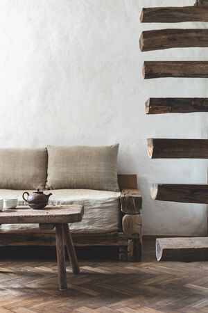 Vertical photo of wooden and cozy house in vintage interior style. Teapot on wood textured table near comfort sofa and retro stairs, against white wall with copy space