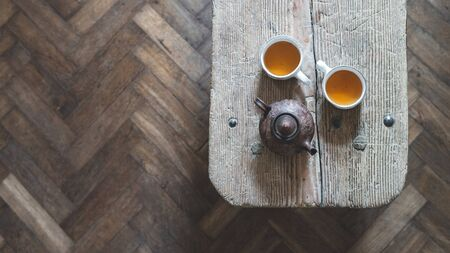 Panoramic top view of ceramic teapot and two cup of tea on wooden table, standing at laminate floor with copy space. Comfort and cozy house with authentic interior design Stock fotó