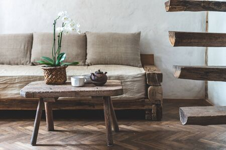Cozy house with wooden interior design. Teapot, cup with beverage and orchid flower on wood textured table, standing near comfort couch, white wall and retro stairs in room with laminate floor