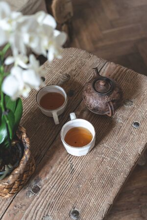 Vertical photo of ceramic teapot, cups with beverage, white orchid flower in flowerpot standing at wooden table. High angle view of element house with laminate floor and vintage interior style