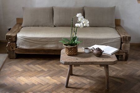 Teapot, cup with beverage, paper book and orchid flower on wood textured table near comfort couch and white wall. Cozy house with wooden interior design in room with laminate floor Stock fotó
