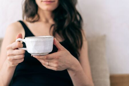 Selective focus of young adult woman holding white cup of beverage in hand. Girl with calm cheerful smile sitting at home near wall with copy space