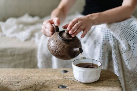 Selective focus of young adult woman holding teapot and pouring tea in white cup. Girl resting on weekend holiday, sitting near wooden table on sofa with plaid and spending free time at cozy home Stock fotó