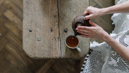 Panoramic top view of young adult woman holding teapot over wooden table with copy space. Girl pouring tea in white cup, sitting on sofa with plaid and spending free time at cozy house