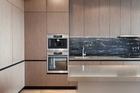 Kitchen wooden facade at cupboard, household appliance, electric oven, coffee machine and sink with chrome water tap in new house. Apartment with modern interior design