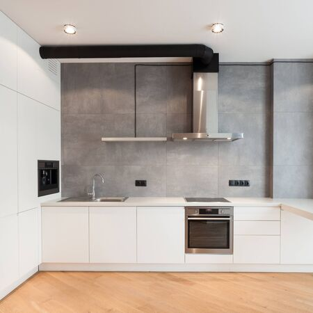 Apartment with contemporary interior. Kitchen in loft style, built in household appliance, electric stove, oven, sink on worktop, wooden laminate on floor and extractor hood on grey wall Banco de Imagens