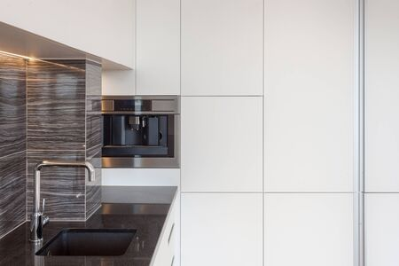 Built in household appliance with coffee machine and sink with water tap in counter table. House with modern interior design at kitchen and white cupboard with copy space Banco de Imagens