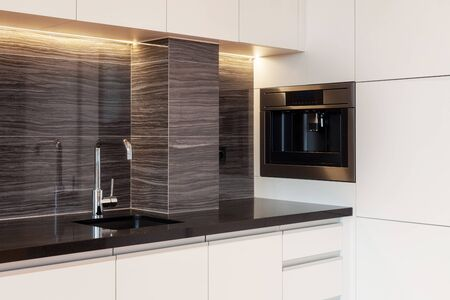Modern apartment with contemporary interior at kitchen with white cupboard. Built in household appliance with coffee machine and sink with water tap in counter table Banco de Imagens