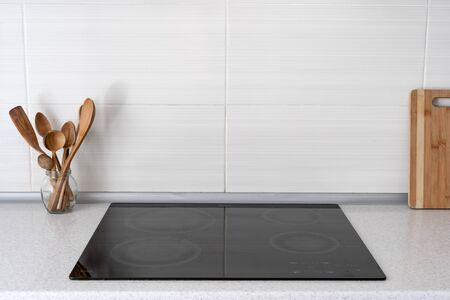 Black ceramic induction stove with wooden flatware. Modern apartment with contemporary interior, built in kitchen appliance and white tile on wall with copy space Banco de Imagens