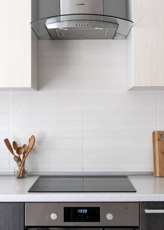 Vertical photo of contemporary home with modern interior, built in kitchen appliance and white tile on wall. Black ceramic induction stove with clean surface and wooden spoon under range hood Banco de Imagens