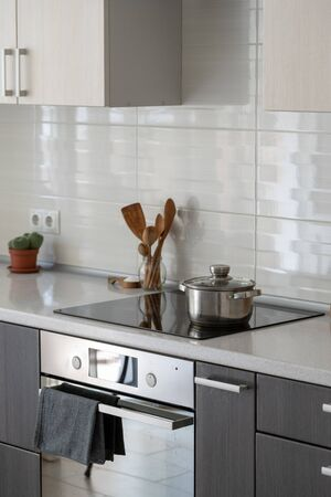 Ceramic induction stove with saucepan on surface, wooden supplies and green plant in flowerpot. Modern apartment with contemporary interior, built in oven, kitchen appliance and white tile on wall