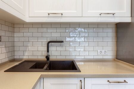 Modern apartment with contemporary interior at kitchen with white cabinet and tile on wall. New house with black water tap and sink on stone countertop