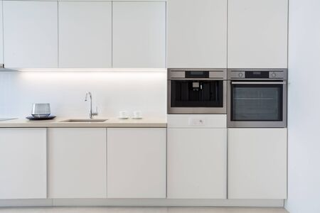 White modern apartment with contemporary interior at kitchen. New household appliance, sink with chrome water tap on worktop, electric oven and coffee machine in glossy cabinet
