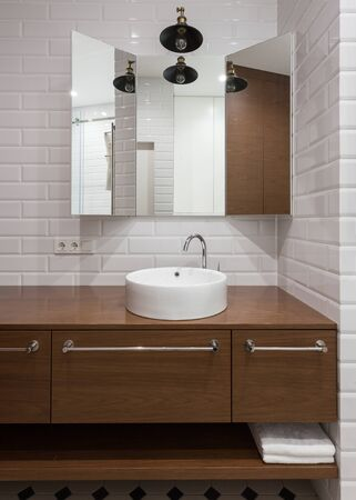 Vertical photo of modern interior design in bathroom. House with wooden facade at cabinet in restroom, large mirror, white sink and wall tile Banco de Imagens