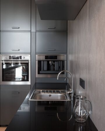 Black kitchen, built in household appliance, electric oven, coffee machine and sink with chrome water tap. Vertical photo of modern apartment with contemporary interior Banco de Imagens