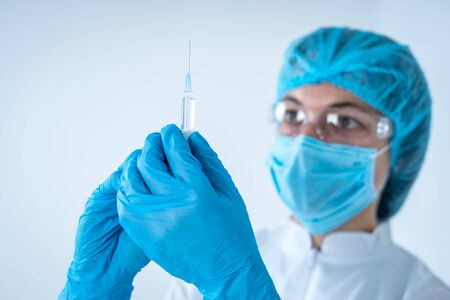 Healthcare development concept. Portrait photo of chemist woman in coat and protective gloves holding syringe in hands, getting ready to make an injection, standing isolated on white background Banco de Imagens