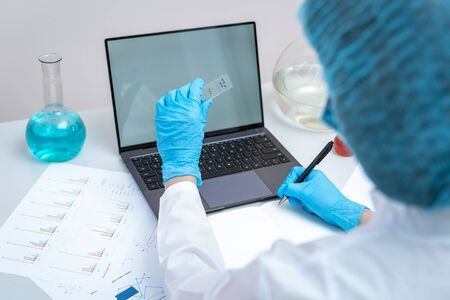 High angle view of scientist woman in coat and protective gloves making clinical experiment, looking at medical glass, sitting in workspace office with laptop computer on desk