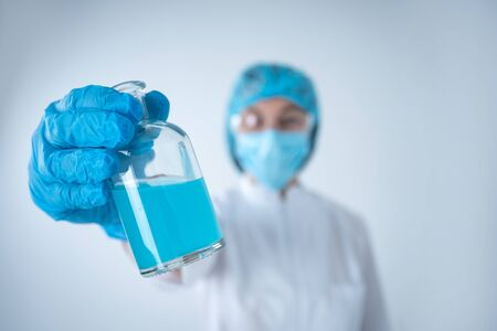 Close up view and selective focus of chemist woman making laboratory analysis, searching vaccine solution, showing medical glass bottle with blue liquid, standing isolated on white background Banco de Imagens