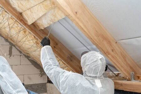 Back view of professional roofer man installing thermal insulation layer with mineral rock wool under the roof. Male in protective overall holding measuring tape near isolation material Banco de Imagens