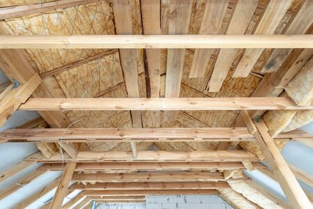 Roof with mineral rockwool in wall section with wooden planks. Low view of house under construction with insulation glass wool on an attic floor