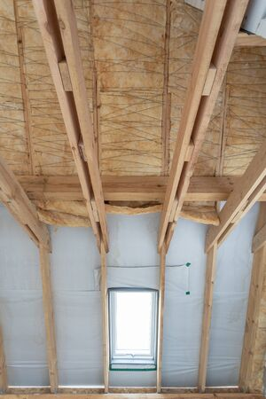 Vertical photo of house under construction with insulation glass wool on an attic floor. Roof with mansard window and mineral rockwool in wall section Banco de Imagens