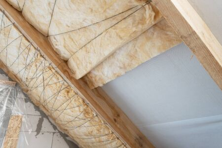 Insulation technology concept. house under construction with isolation glass wool on an attic floor. Roof with mineral rockwool in wooden plank wall section