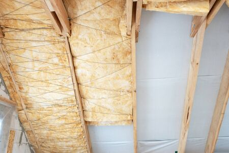 Concept of energy efficient technology. Low angle view of house under construction with insulation glass wool on an attic floor. Roof with mineral rockwool in wall section