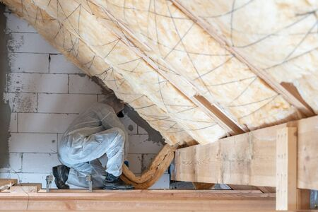 Profile view of professional workman in protective workwear installing thermal insulation layer under the roof, fixed materian on wall