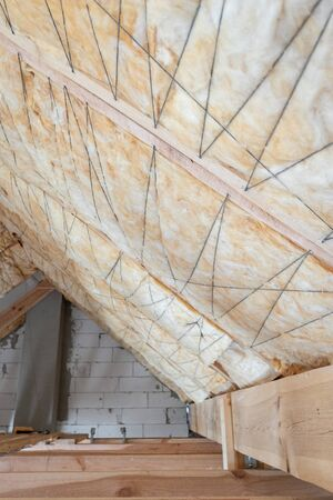 Vertical photo of house under construction with insulation glass wool on empty attic floor. Roof with fixed layer of mineral rockwool in wall section