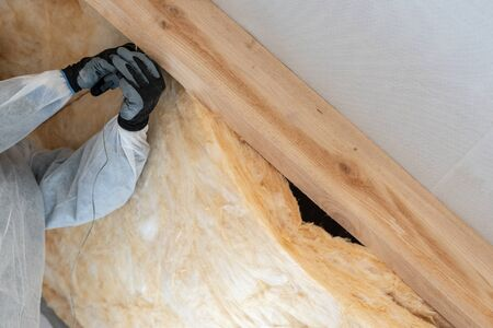 Cropped view of professional worker man in protective overall installing thermal insulation layer with fiberglass wool under the roof, using construction stapler and fixed material in wooden section