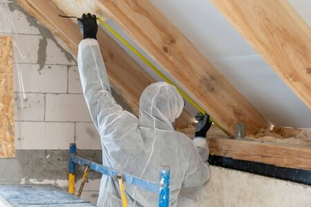 Back view of professional builder man in protective overall holding measuring tape, installing thermal insulation layer with mineral rock wool under the roof Banco de Imagens